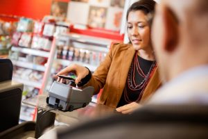 Customer paying for purchase with mobile phone, an example of EPOS Software for Retail Contactless Technology