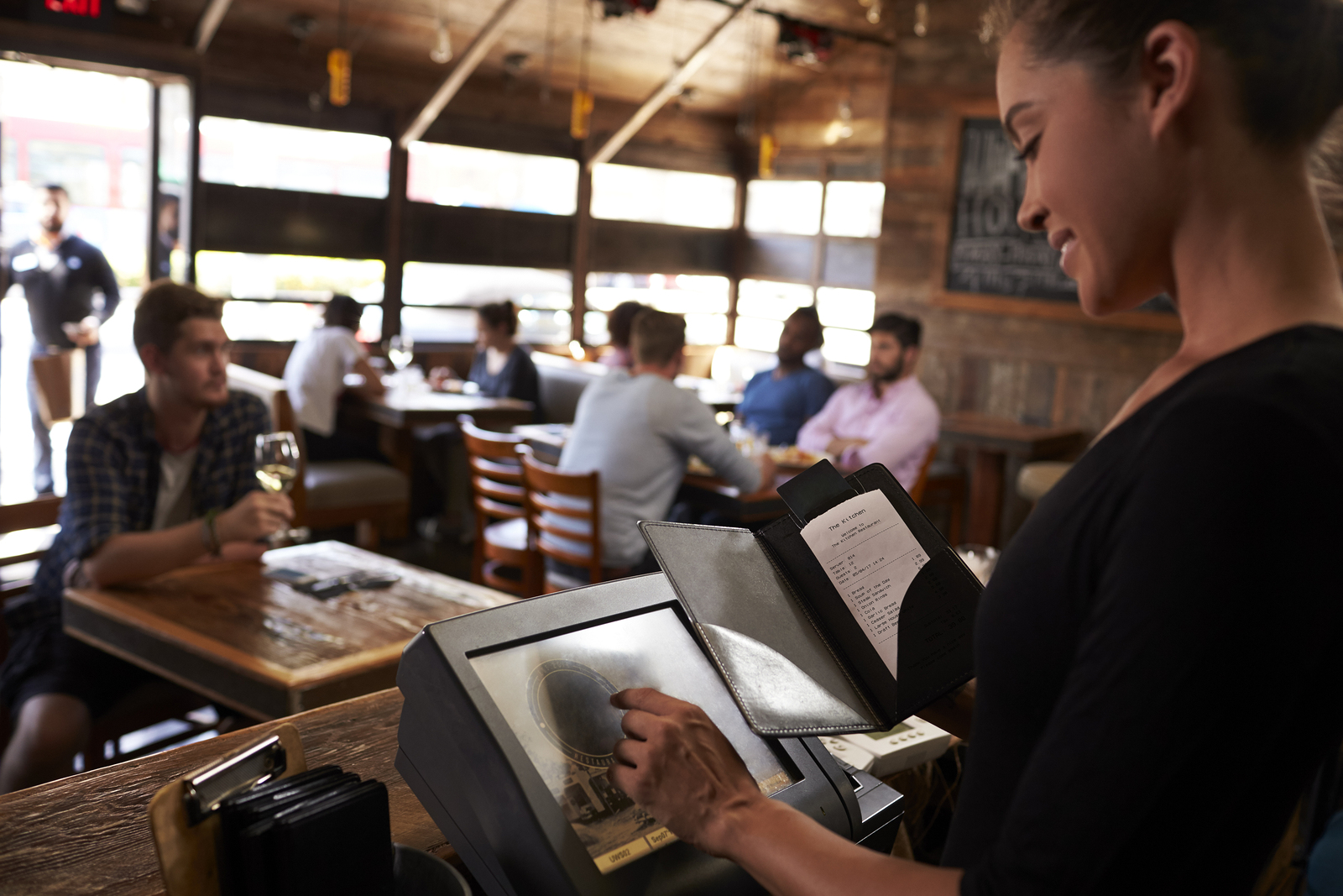 EPoS Software - Young woman preparing bill at restaurant using touch screen